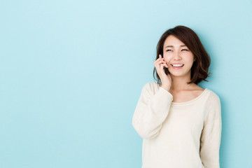attractive asian woman talking on blue background
