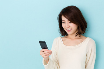 attractive asian woman using smart phone on blue background