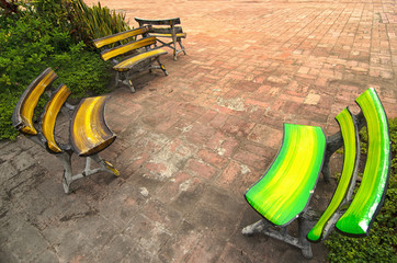 Few colorful benches oposit each other on a brick square - tradi