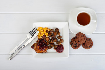 plate of food and a cup of tea on a white wooden background