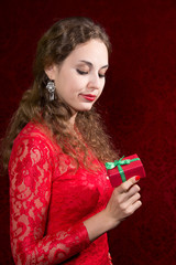 Beautiful girl dissatisfied with a small gift in a red dress