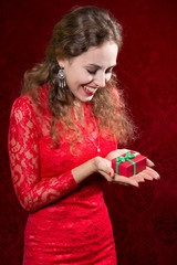 Happy young woman with a small gift in a red dress.