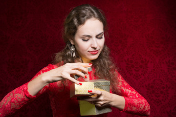 Beautiful girl dissatisfied with a small gift in a red dress.