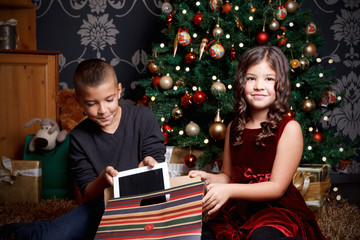 Happy children opening a Christmas gift
