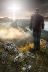 Man on top of the mountain looking at Christian Cross at sunrise