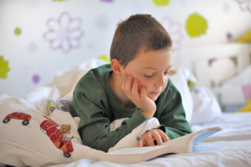 Young Boy Reading a Book in Bed