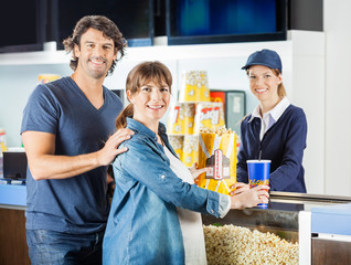 Expectant Couple Buying Snacks From Seller At Cinema Concession