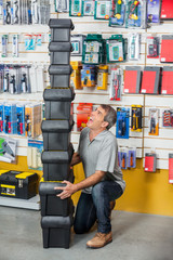 Man Shouting While Carrying Stacked Toolboxes In Store