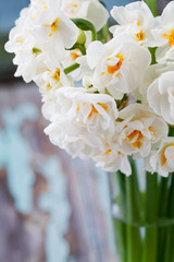 Beautiful bouquet of bridal daffodils on old wooden table