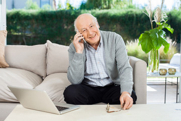 Smiling Senior Man Answering Smartphone At Nursing Home Porch