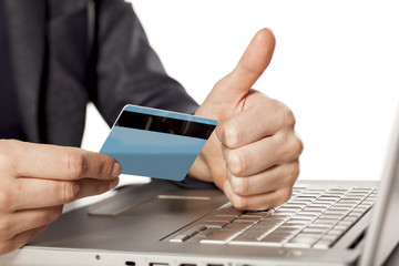 Female hands holding  a credit card and showing thumbs up
