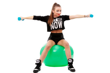 young sporty woman sitting on fitball with dumbbells on white ba