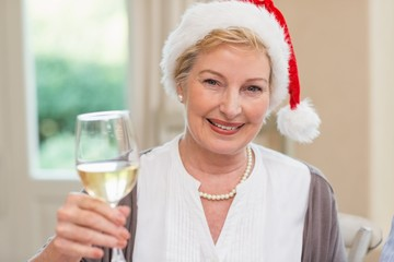 Smiling mature woman in santa hat toasting with white wine