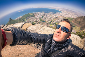 Handsome young man taking selfie at Table Mountain in CapeTown