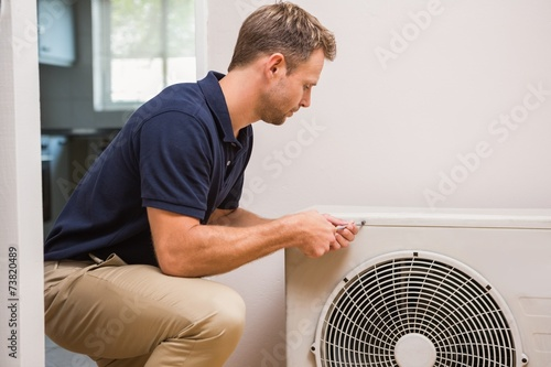 Focused handyman fixing air conditioning - 73820489