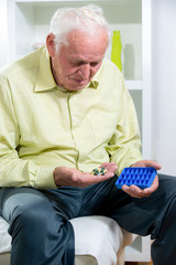 Senior man uses a pill organizer to prepare his medication