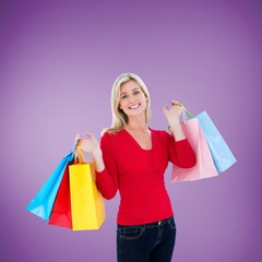 Composite image of happy blonde holding shopping bags