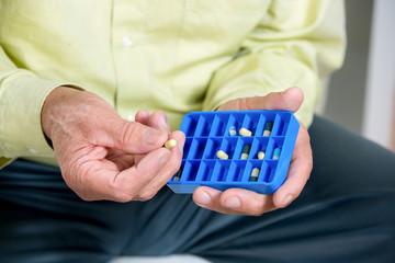 Senior man uses a pill organizer to prepare his medication
