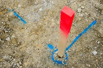 Pflock und blaue Markierung auf Baustelle