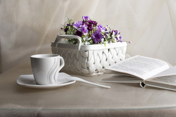 Teacup, teaspoon, vase with violet flowers and book