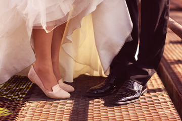 Bride and groom legs on a bridge