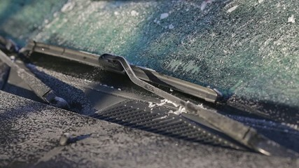 Scraping ice from a windshield close up