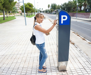 young woman paying for parking at pay station