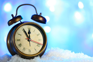Alarm clock in snow on bright background