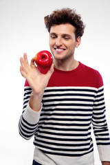 Portrait of a happy man holding red apple over gray background