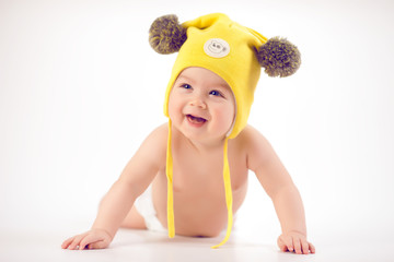 Baby in yellow winter hat lying on the floor