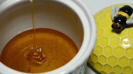 Honig fließt in einen Honigtopf