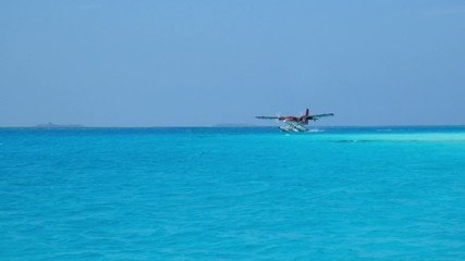 Seaplane makes landing on water. Maldives Indian Ocean.