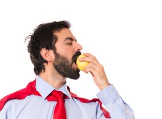Businessman dressed like superhero eating an apple