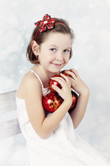 Cute girl with freckles on her nose holding christmas balls