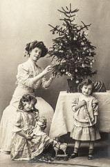 happy mother and children with christmas tree and antique toys