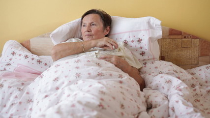 Sick senior woman checking temperature with thermometer in bed.