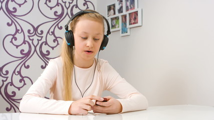 Young girl listening to music and singing