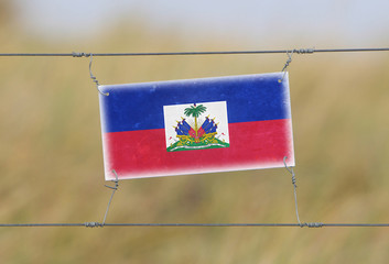 Border fence - Old plastic sign with a flag