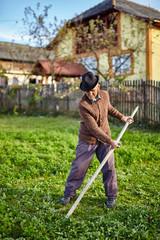 Senior farmer mowing the yard
