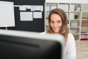 motivierte frau am arbeitsplatz schaut auf pc