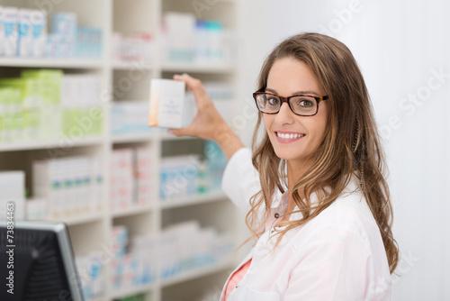 apothekerin zeigt ein medikament - 73834463
