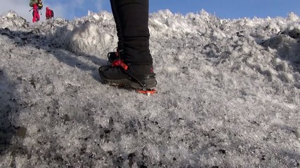Boots with crampons. Man climbs the ice