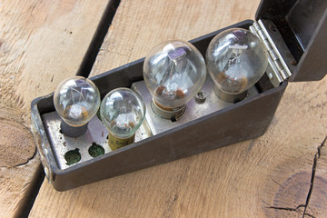 Box with set of old bulbs on wooden background