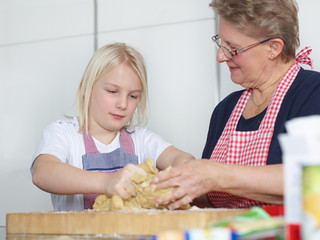 Grandmother and child bake biscuits