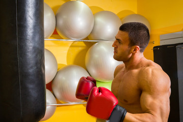 Muscular man in the gym. The man in boxing gloves, hit a punchin