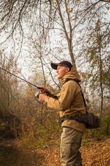 Fisherman on the river bank. Autumn fishing.