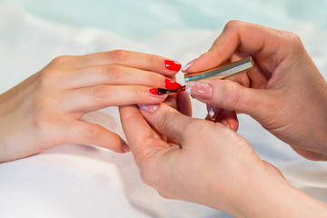 Manicure. applying red nail polish