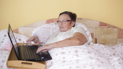Elderly woman using laptop in bed at home.