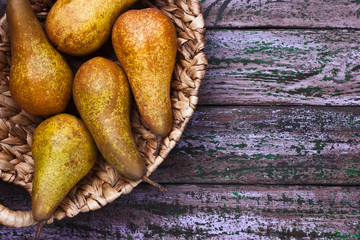 Pears in a braided bowl on a purple background