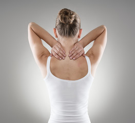 Portrait of young woman massaging her painful neck